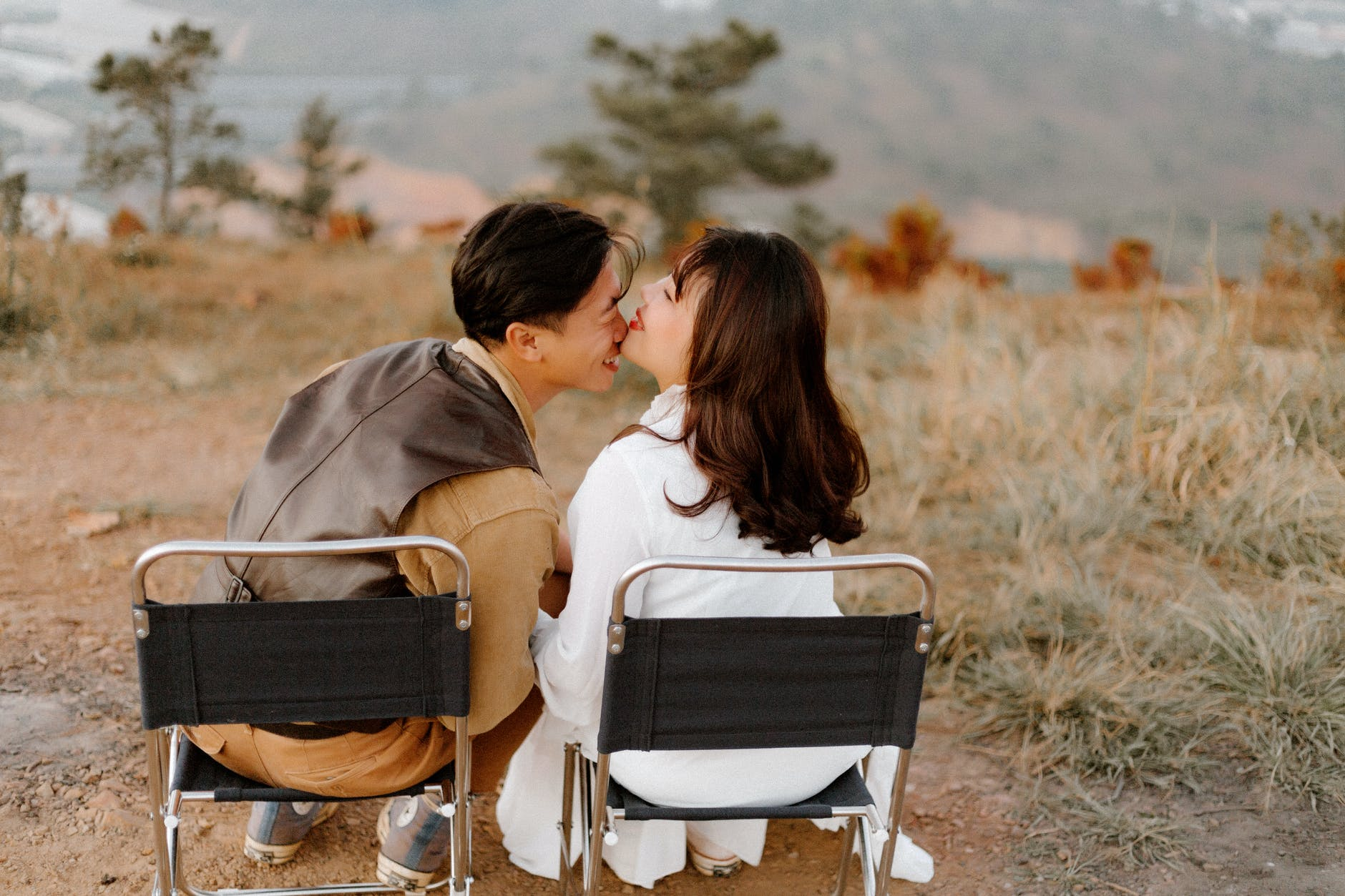 asian wedding couple on chairs in nature